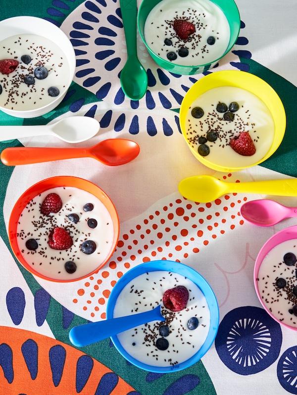 Linguri KALLAS de diverse culori și boluri KALLAS cu iaurt și fructe, pe o față de masă multicoloră.