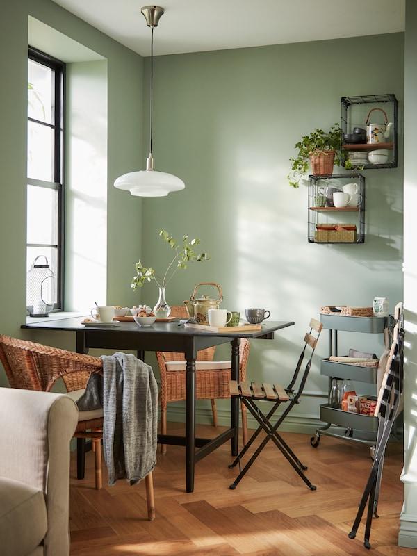 Într-un colț o zonă mică pentru luat masa, pereți verzi, o masă cu extensie cu ceai pe ea, fotolii din ratan, o lustră albă.