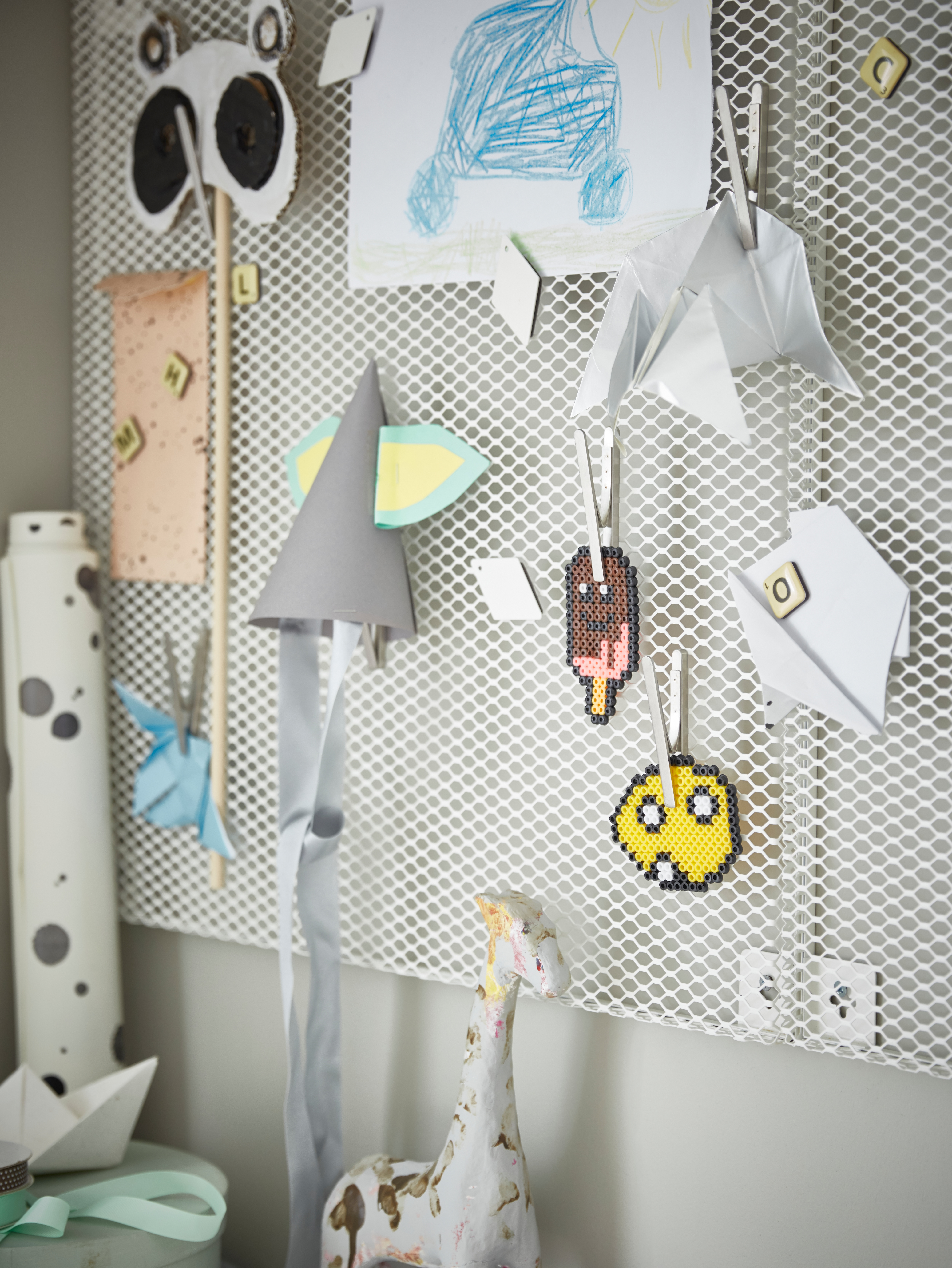 A white SÖDERGARN memo board with magnets is mounted on a wall, holding children's crafts and drawings. Some are on clips.
