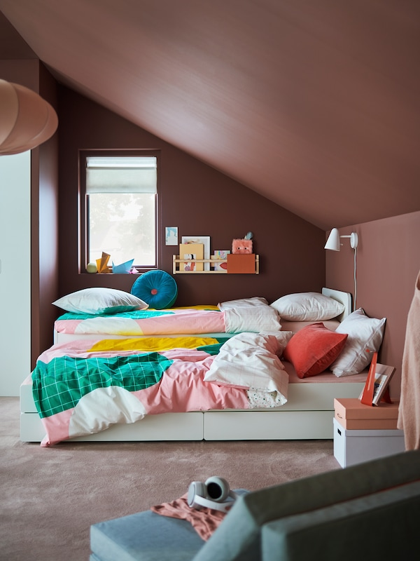 A kids' room, painted brown, with a sloping ceiling with a SLÄKT bed and its underbed with MÖJLIGHET bed linen.