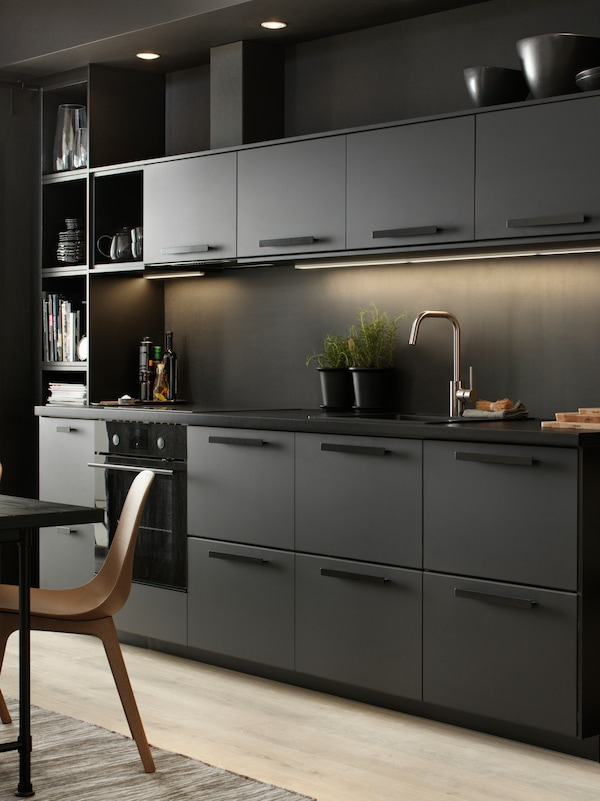 A sleek black kitchen with lighting under the top cupboards. Two black pots with plants inside stand on the counter.