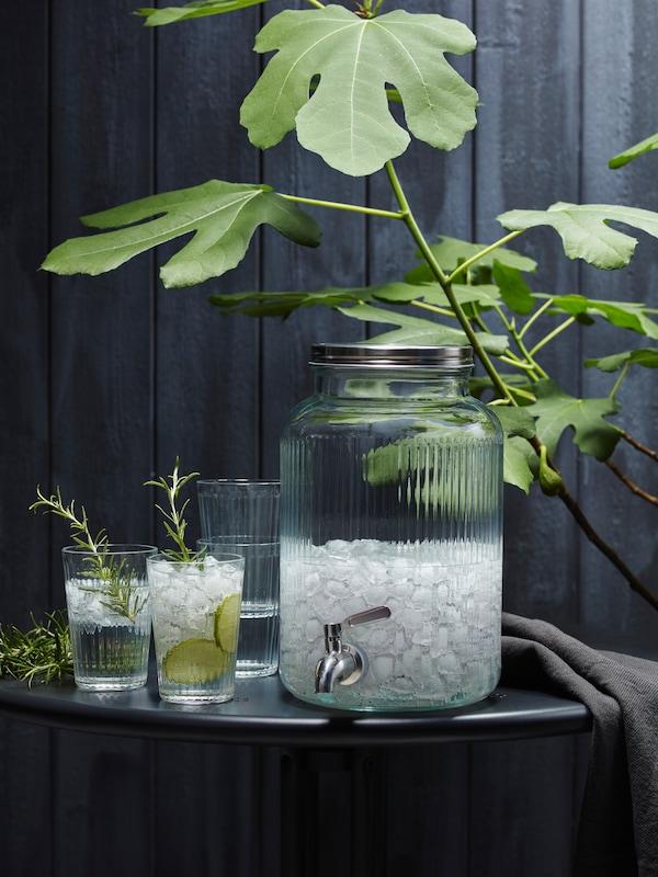 Serahi VARDAGEN berisi smoothie hijau di atas meja di sebelah dua tindanan gelas yang kosong dan satu gelas separa penuh.