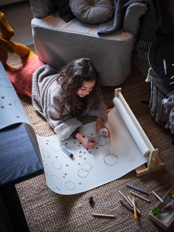 Een meisje ligt op de vloer tussen een grijze fauteuil en een tafel. Ze tekent op een MÅLA rol tekenpapier die deels op de tafel ligt.