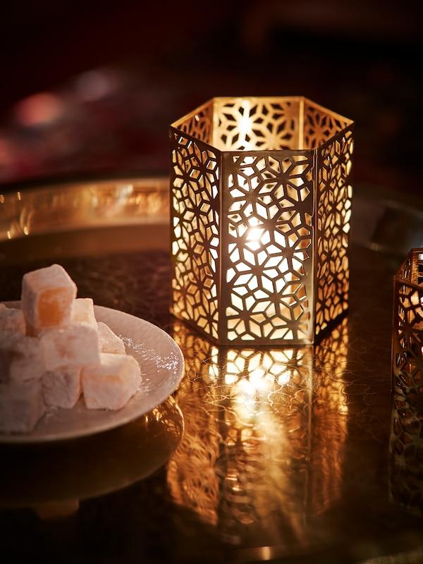 une lanterne dorée est posée sur une table avec une bougie à l'intérieur qui éclaire la pièce