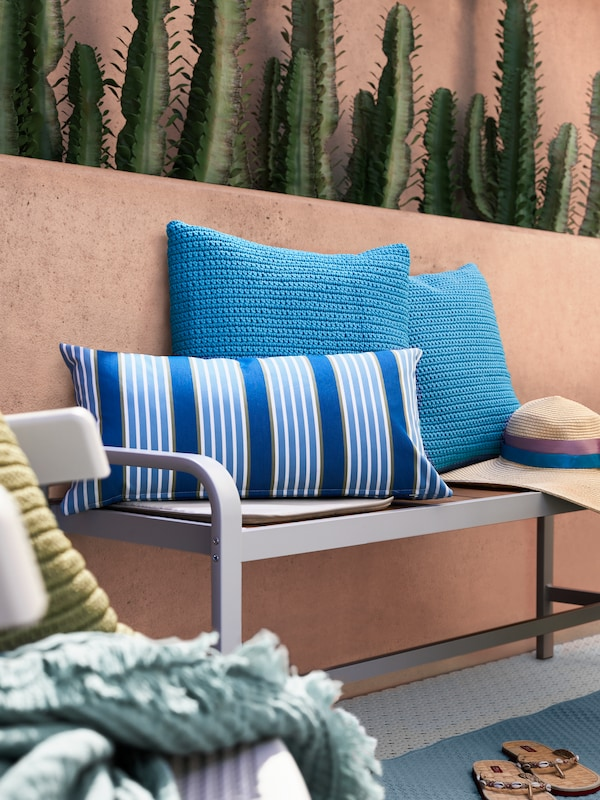 Une housse de coussin rouge FESTHOLMEN et un plaid POLARVIDE bleu clair créent un petit cocon douillet avec des peluches sur un balcon.