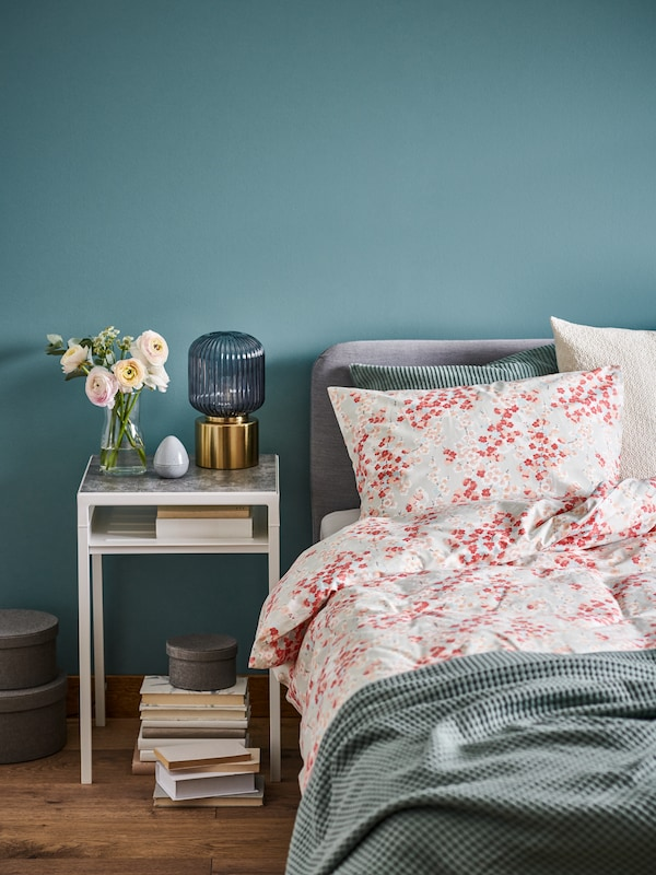 Semi-neatly made bed with floral-patterned KLIBBGLIM bed linen. A vase with flowers and a SOLKLINT lamp on the bedside table.
