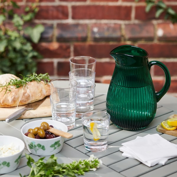 A dark green glass pitcher placed on an outdoor table, with stacked glasses and a bowlful of olives.