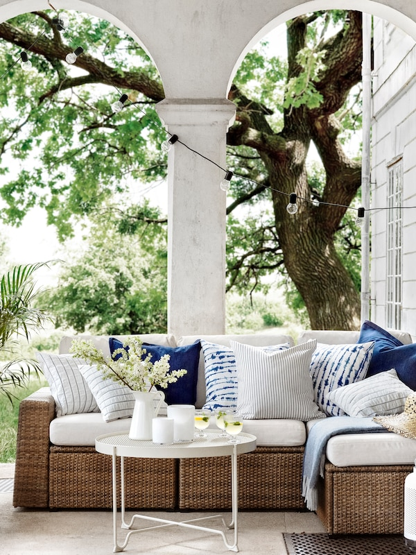 A sofa with white upholstery with various colored and patterned scatter cushions placed outside with hanging lights.