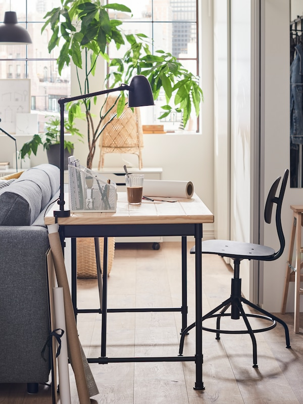 A desk with wooden top and black legs, a glass, a potted plant and other items, a swivel chair and the back of a sofa.