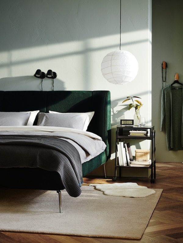 A green TUFJORD upholstered bed with light grey bed linen and a dark grey throw on a beige rug, beside a bedside table.