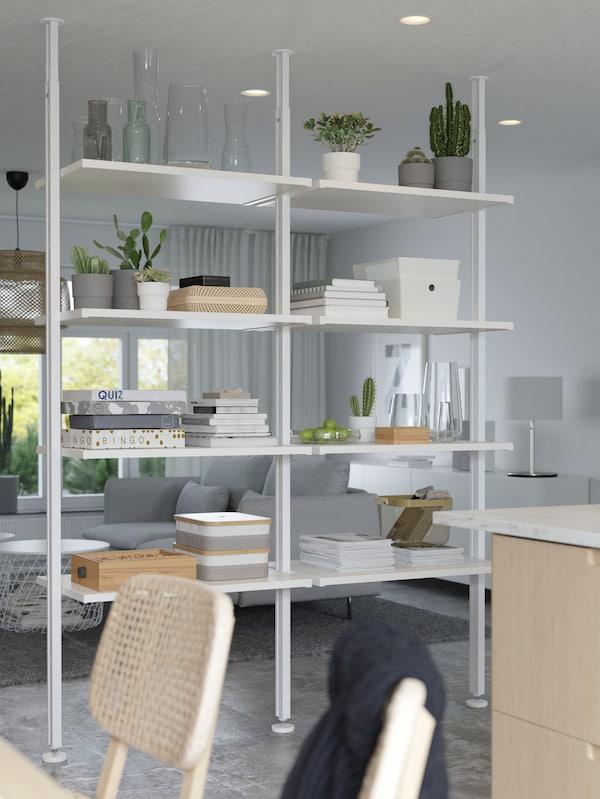Hvitt hyllesystem med bøker, spill, potteplanter, esker og andre ting, brukt som romavdeler mellom ei stue og en spiseplass.