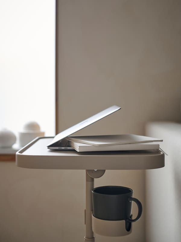 Närbild på BJÖRKÅSEN laptopställ med en nerfälld dator och kopp under.