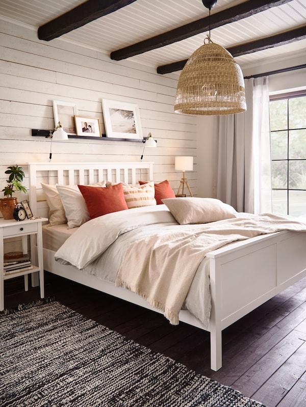 Cama HEMNES blanca con cojines marrones y beige, y ropa de cama BERGPALM. Hay una alfombra negra y blanca en el suelo.