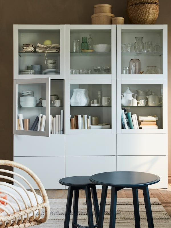 A white storage combination with glass-doors and drawers, and a dark blue-green nest of two tables.