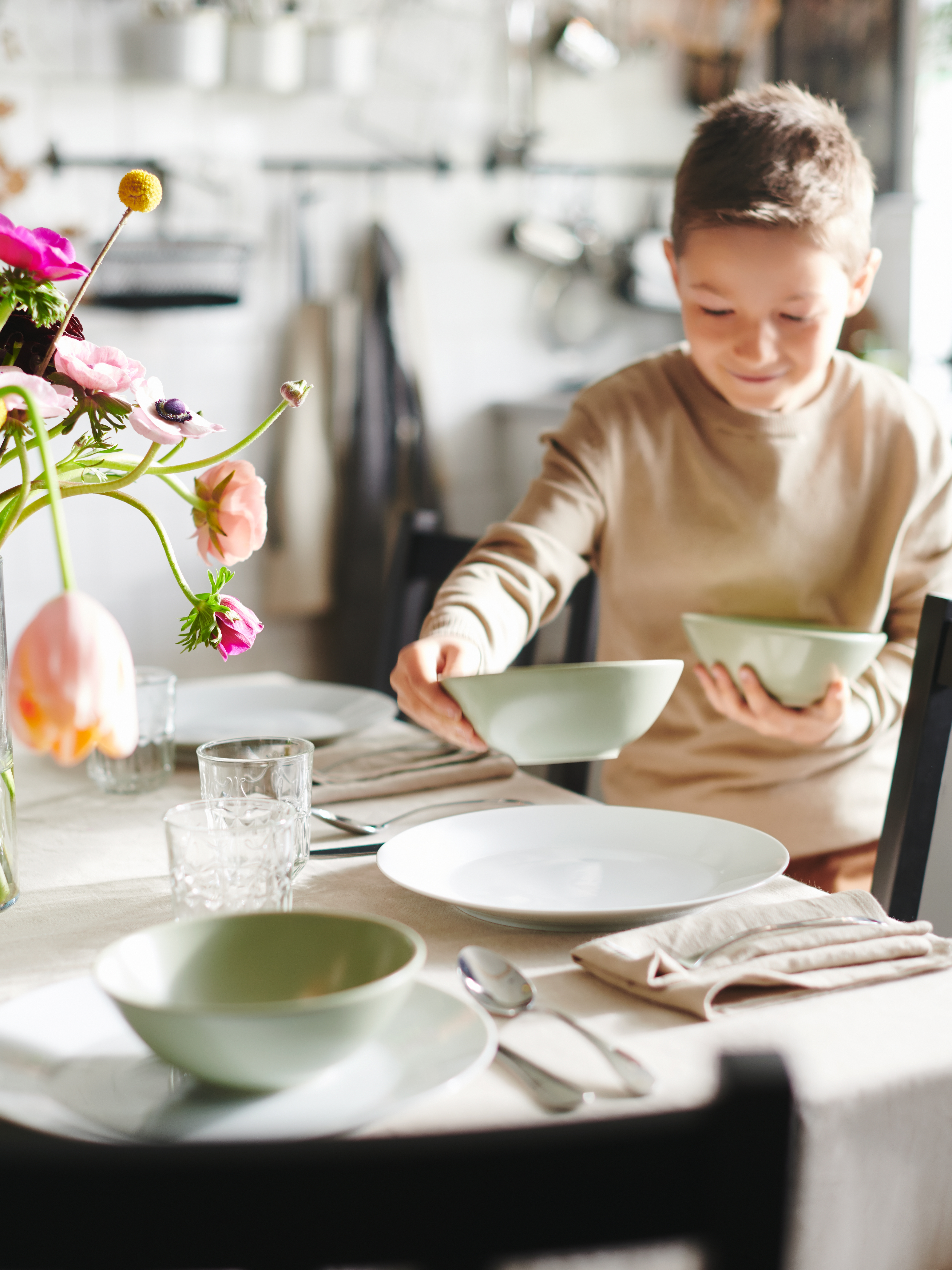 A sunlit table with a tablecloth and flowers is being set by a boy distributing matt-green FÄRGKLAR bowls onto white plates.