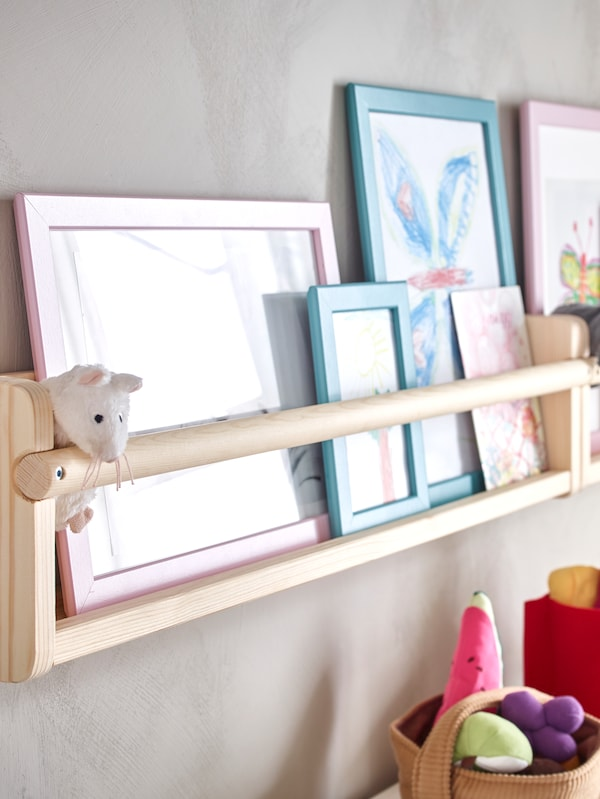 FLISAT wall storage attached to the wall holds children's drawings in FISKBO frames and a little soft toy mouse.