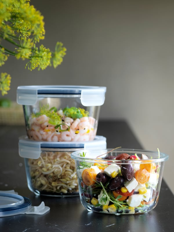 3 round glass food containers with plastic lids storing shoots, a salad and prawns.