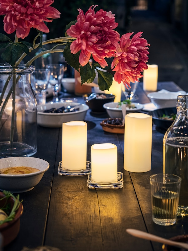 A table with LED block candles, a glass jar with flower blooms, and diverse items like glasses, a bottle and dishes.