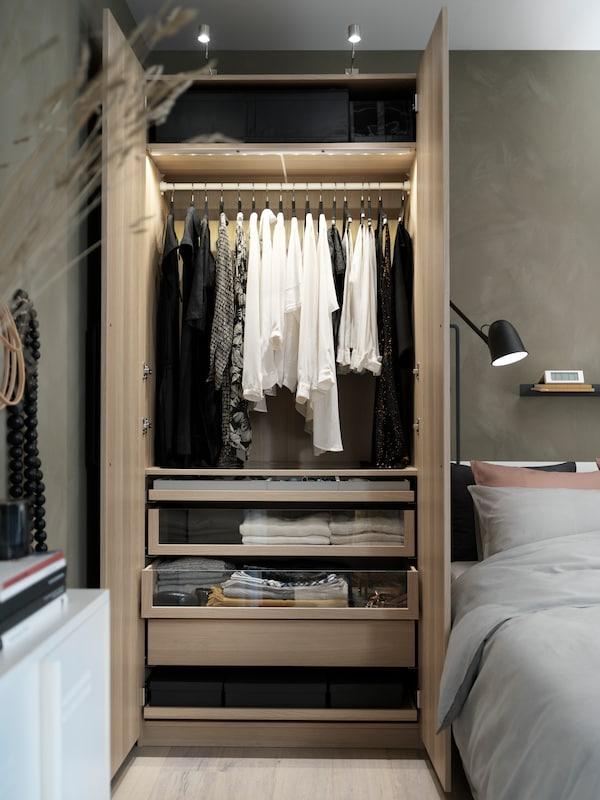 Combinación de armario PAX/FORSAND con cajones junto a una cama. Las puertas están abiertas y hay ropa colgada en una barra.