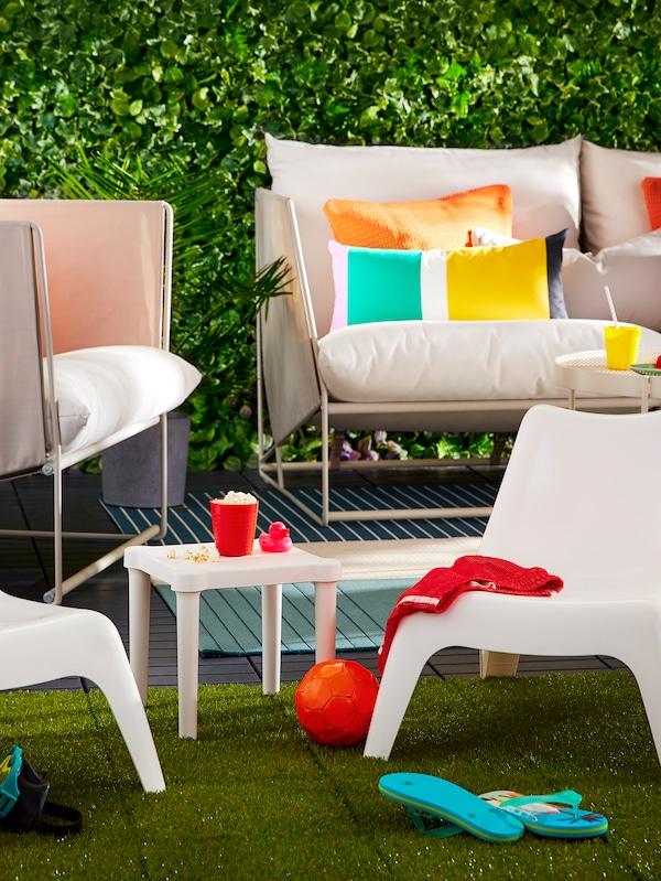 Des meubles d'extérieur comprenant un canapé, un fauteuil, des petits fauteuils pour enfants et une table avec des coussins et divers articles.