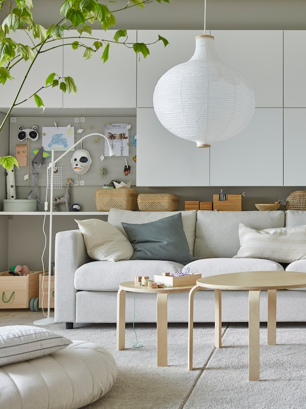 SVALSTA nest of tables, a set of two, stand on two rugs placed together in front of a VIMLE sofa under a RISBYN pendant lamp.