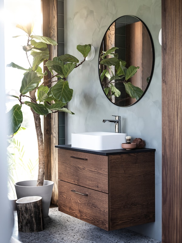 A bathroom with a GODMORGON vanity unit in dark brown wood, an oval mirror on the wall above and a potted ficus on the floor.