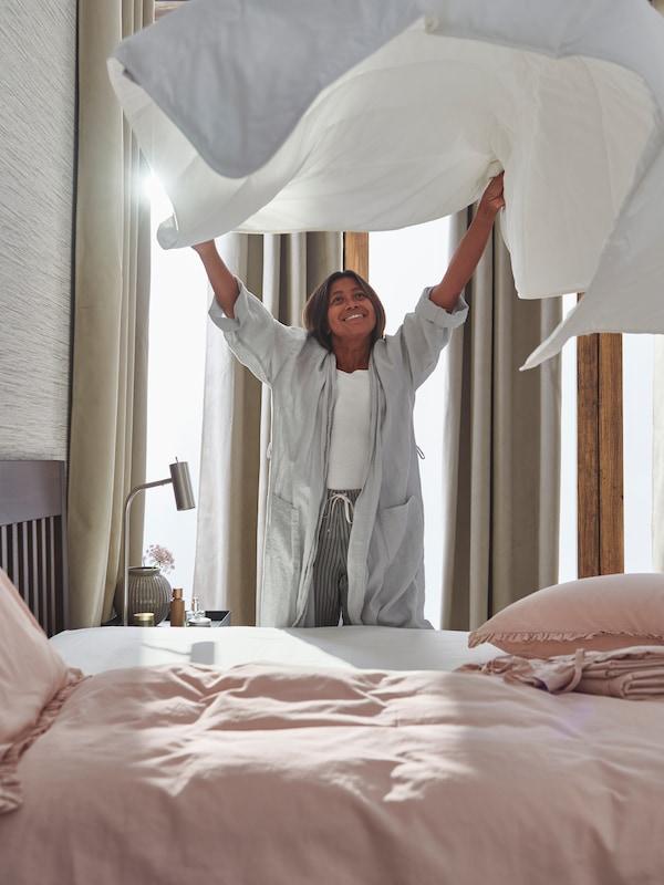 Žena postavlja krevet sa svijetlorozom KRANSKRAGE posteljinom i protresa STJÄRNBRÄCKA poplun u zraku iznad kreveta.