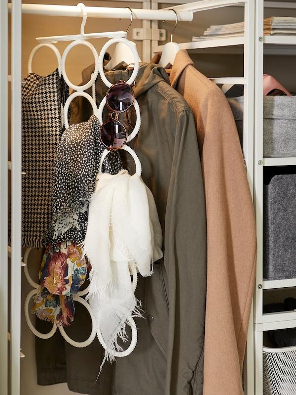 Halsdukar på KOMPLEMENT klädbetjänt och multihängare och kläder hängande på BUMERANG galgar.