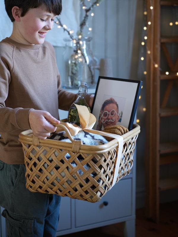 Garçon tenant un panier INSVEP en rotin avec des poignées rempli de cadeaux, y compris un cadre LOMVIKEN noir.