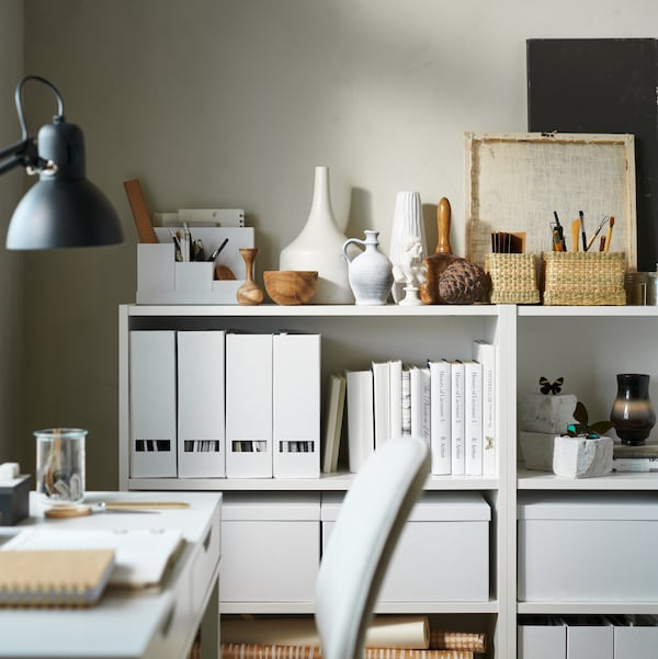 Two white BILLY bookcases holding white TJENA magazine files, white TJENA storage boxes with lids and several small items.