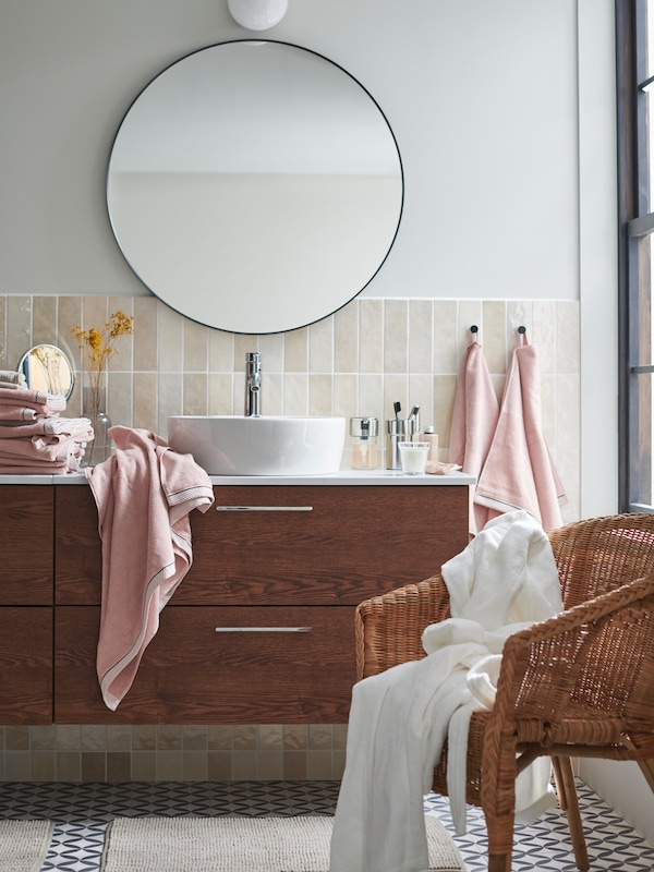 A round mirror on a bathroom wall above a storage unit with towels and diverse other bathroom articles.