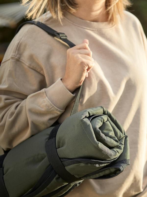 Una mujer transportar la manta para pícnic FJÄLLMOTT perfectamente plegada y colgada del hombro con sus prácticas correas.