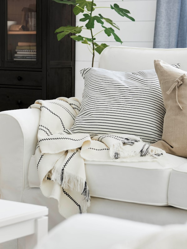 Cushion with INGALILL cover, white with dark grey stripes and cushion with a beige AINA cover on a white EKTORP sofa.