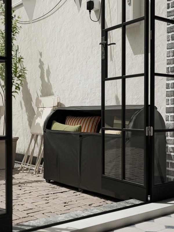 Grande custodia nera da esterno, contenente cuscini verdi e un cuscino arancione, appoggiata a una parete bianca accanto a una porta a vetri aperta.