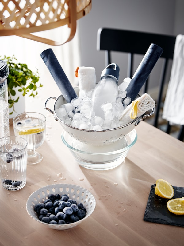 A water bottle and some washcloths sit in a GEMAK colander full of ice cubes on a table, along with glasses and fruit.