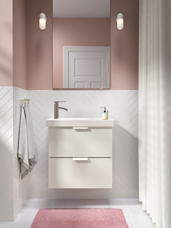A white GODMORGON sink vanity with pink bathroom accessories.