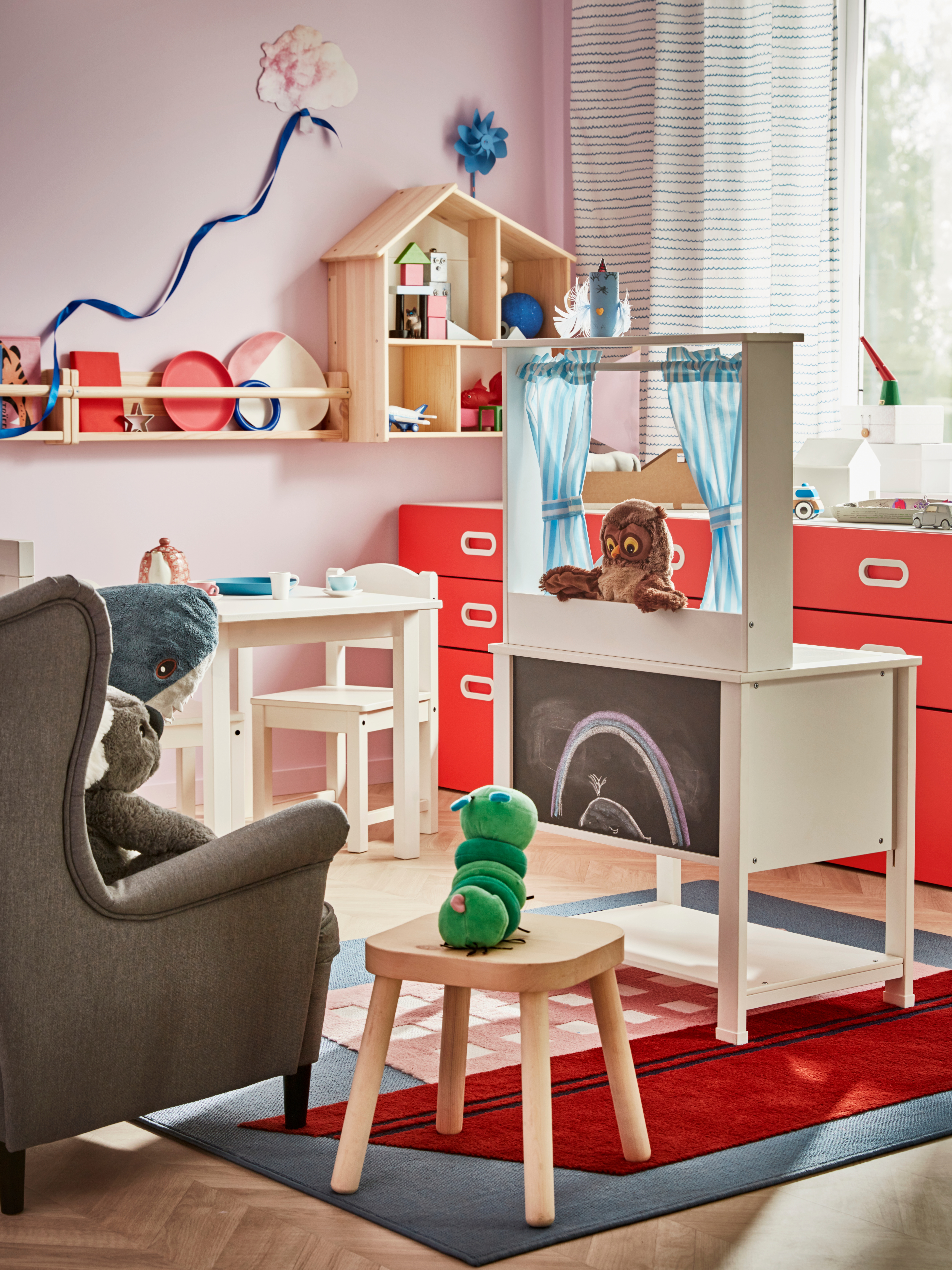 A children's room with an audience of soft toys on chairs watching an owl puppet in a SPISIG play kitchen with curtains.
