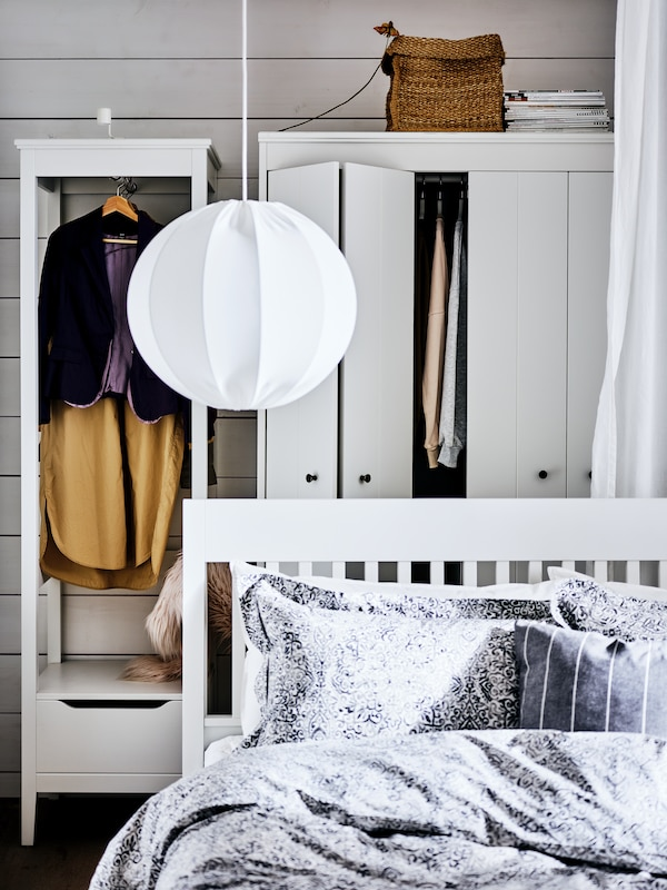 A white IDANÄS bedframe with a pendant lamp above it, in front of two white wardrobes with hanging clothes on show.