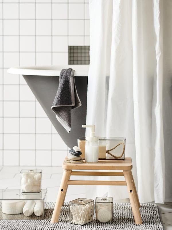 Valkoinen kylpyhuone, jossa on FINTSEN-kylpyhuonematto. Maton päällä on VILTTO-jakkara jonka päällä on TACKA-saippuapumppu sekä GODMORGON- kannellisia laatikoita.