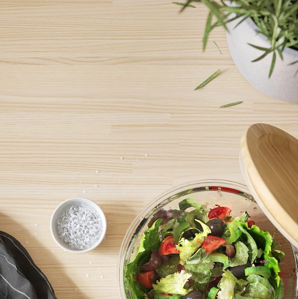A bowl of salad and a small bowl of salt stand on a wooden worktop.