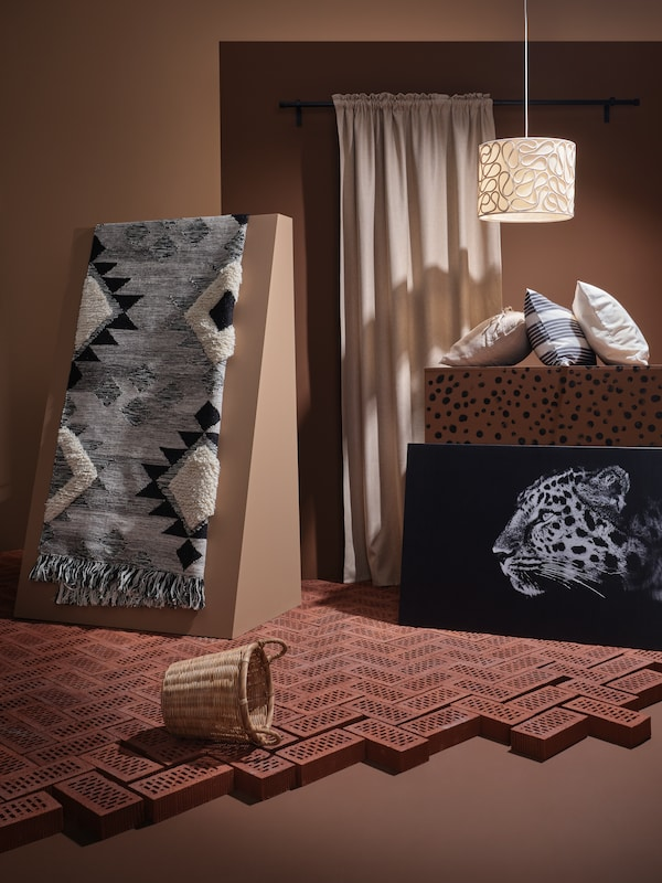An artistic display featuring a TANNISBY handmade wool rug on a slanted podium, ANNAKAJSA curtains and a BJÖRKSTA print.