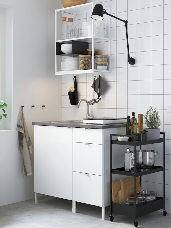 An ENHET kitchen with white open and closed storage, with a black ENHET trolley beside it.