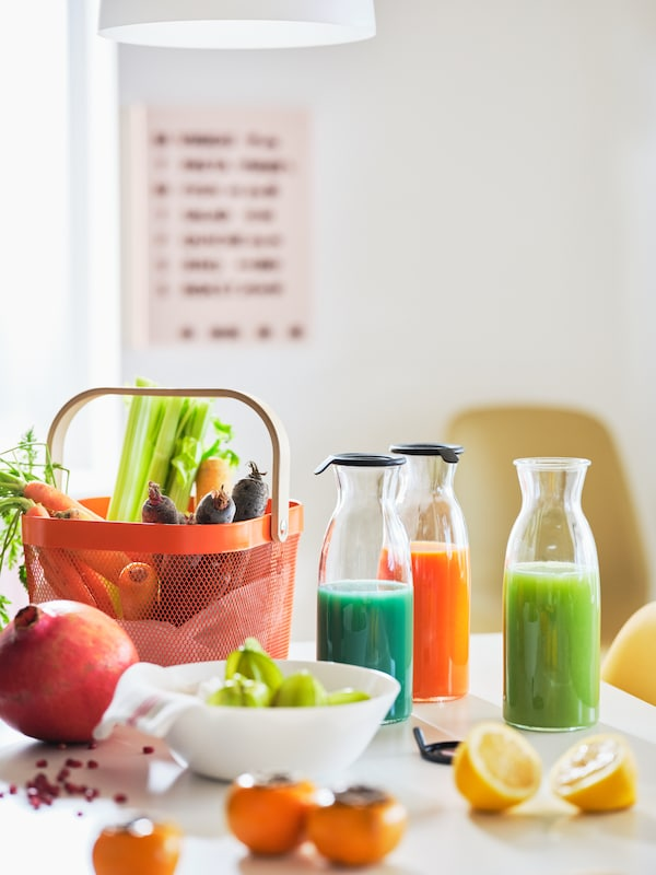 A white tabletop with a RISATORP basket and a colour-bursting mix of vegetables, fruits and juices in clear-glass carafes.