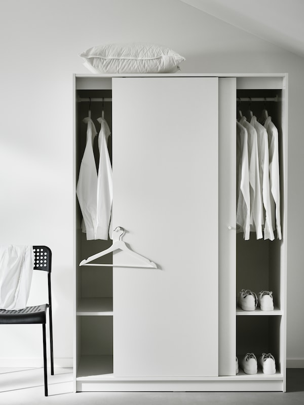 A white KLEPPSTAD wardrobe with both the doors open, showing white shirts on the hanging rails. A black chair is beside it.