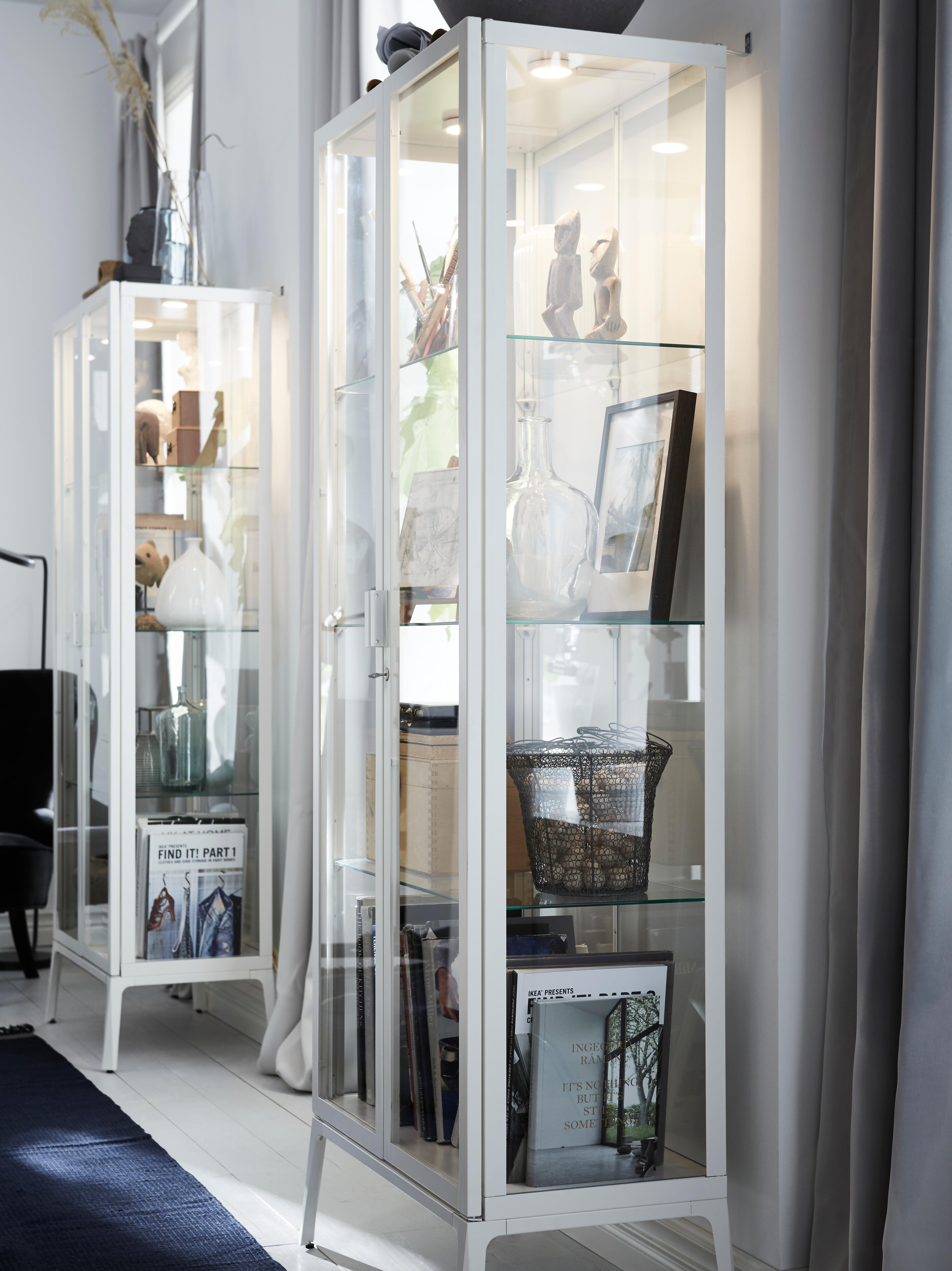Ai lati di una finestra, due vetrine bianche illuminate sono addossate alla parete e contengono libri, vasi e altri oggetti.