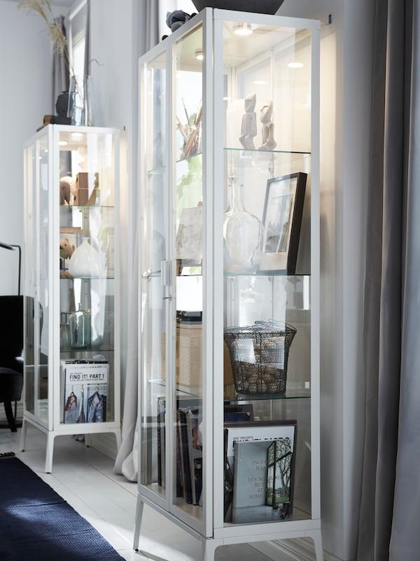 Corp cu uși din sticlă MILSBO, cu margini albe, de la IKEA, și iluminat integrat în interior, care folosesc corpuri de iluminat VAXMYRA cu LED.