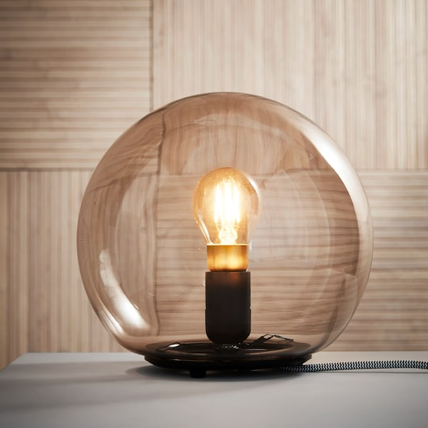 A lamp in the form of a glass ball with a single bulb inside, on a grey surface in front of brown wooden panelling.