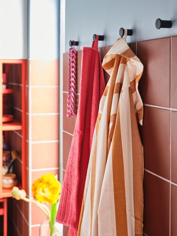 Pixama rosa e laranxa de raias, unha toalla de baño de cor vermella clara e un colar rosa penduran en pequenos colgadoiros negros montados na parede.