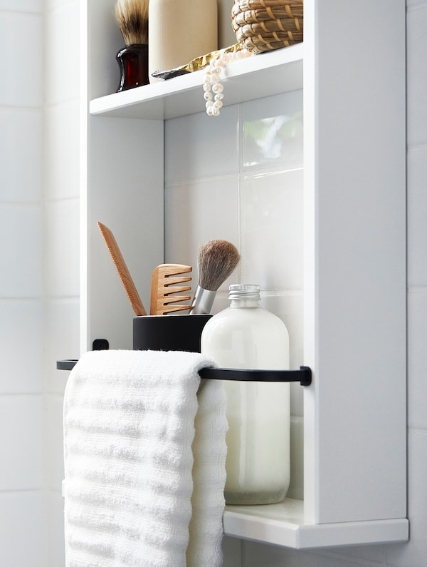 A white HEMNES wall shelf with various bathroom products on it and a white towel on a black bar.