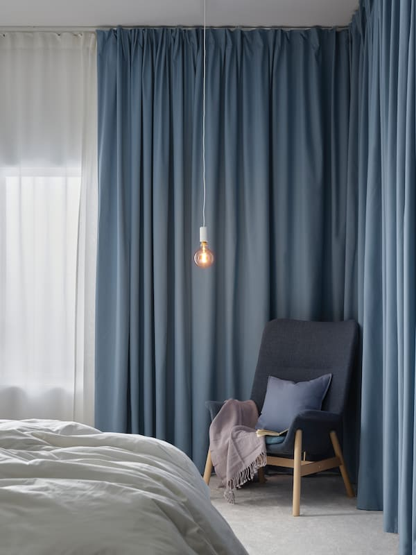 A blue chair accompnaied by a blue cushion and curtain, creating a cozy blue corner.
